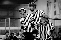 Three referees lean in to get a better view of the skaters.  From front to back: Lollerskates (a jammer referee), Cameltron (back pack referee and head referee), and Override (a jamer referee).