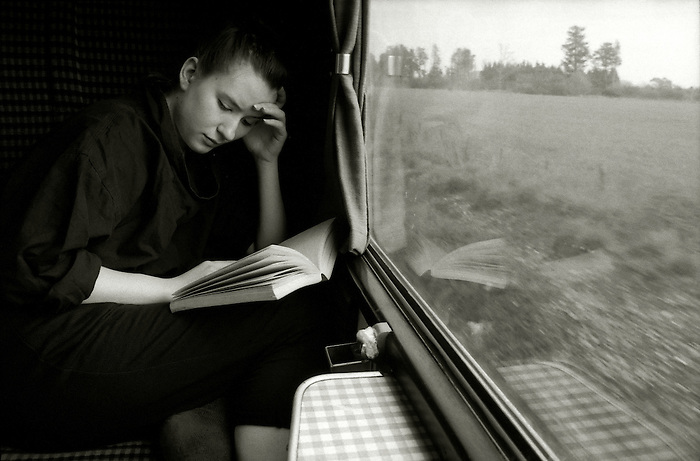 a young woman reading a novel on a train journey.<br />
