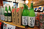 Bottles of sake are lined up on the shelves of a store inside Tamagawa sake brewery in Kyoto, Japan. More than 1,200 sake breweries exist in Japan, though falling domestic consumption has lead some to look to  overseas markets. Photographer: Robert Gilhooly