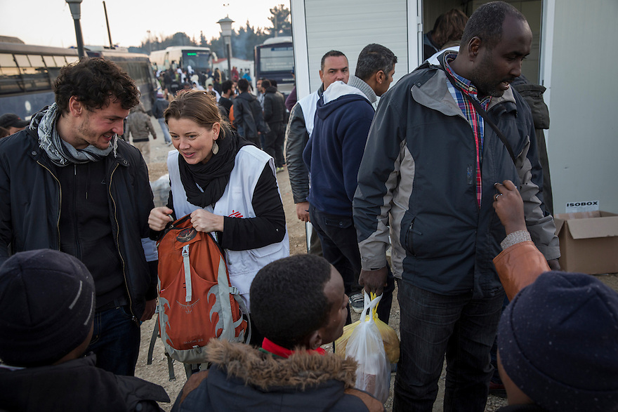 An MSF volunteer speaks with immigrants gathered outside the MSF container clinic at Idomeni camp in Greece.