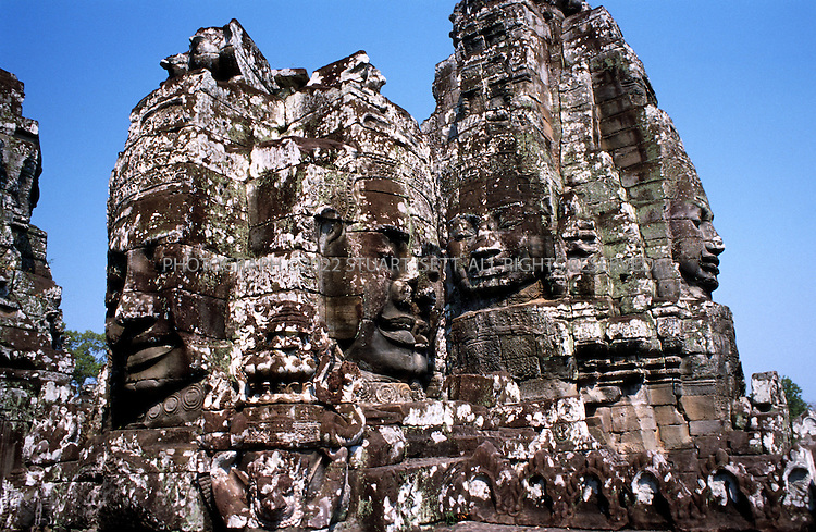 4/20/2003--Angkor Wat Temples, Siem Reap, Cambodia ..BAYON.Prasat Bayon was built in late 12th century to early 13th century, by the King Jayavarman VII, dedicated to Buddhist..BACKGROUND.The Bayon vies with Angkor Wat the favorite monument of visitors . the two evoke similar aesthetic responses yet are different in purpose, design, architecture and decoration. The dense jungle surround the temple camouflaged its position in relation to other structures at Angkor so it was not known for some time that the Bayon stands in the exact centre of the city of Angkor Thom. Even after this was known, the Bayon was erroneously connected with the city of Yasovarman I and thus dated to the ninth century. A pediment found in 1925 depicting an Avalokitesvara identified the Bayon as a Buddhist temple. This discovery moved the date of the monument ahead some 300 years to the late twelfth century. Even though the date is firmly implanted and supported by archaeological evidence, the Bayon remains one of the most enigmatic temples of the Angkor group. Its symbolism, original form and subsequent changes and constructions have not yet been untangled...The architectural scale and composition of the Bayon exude grandness in every aspects. Its elements juxtapose each other to create balance and harmony. Over 2000 large faces carved on the 54 tower give this temple its majestic character. The faces with slightly curving lips, eyes placed in shadow by the lowered lids utter not a word and yet force you to guess much, wrote P Jennerat de Beerski in the 1920s. It is generally accepted that four faces on each of the tower are images of the bodhisattva Avalokitesvara and that they signify the omnipresence of the king. The characteristics of this faces - a broad forehead, downcast eyes, wild nostrils, thick lips that curl upwards slightly at the ends-combine to reflect the famous 'smile of Angkor'...All photographs ©2003 Stuart Isett.All rights reserved.This image may not be reproduced without e