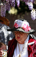 22March2008: Ocean Beach, California, USA. Cordelia Ridenour wears a flower covered hat as she passes underneath the 100-year old wisteria plant at the home of Ned Titlow during the Ocean Beach Historical Society annual Wisteria Tea Party.