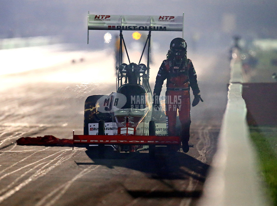 Sep 5, 2015; Clermont, IN, USA; NHRA top fuel driver T.J. Zizzo walks from his car after an engine explosion and fire during qualifying for the US Nationals at Lucas Oil Raceway. Mandatory Credit: Mark J. Rebilas-USA TODAY Sports