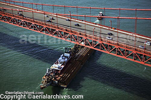 aerial photograph tug and barge passing under Golden Gate bridge, San Francisco, California
