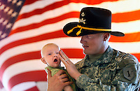 Private First Class Lucas Leach (cq), age 20, holds his 3 month-old son Damian Leach (Cq) at the conclusion of the ceremony for his unit at Fort Carson. Lucas, originally from Utah, will be deployed as a helicopter crew chief, on his first tour in Iraq. ..Soldiers of the 1st Squadron, 6th Cavalry Regiment cased the unit's colors in a ceremony on August 22, at Butts Army Airfield in Fort Carson..The squadron is scheduled to deploy in support of Operation Iraqi Freedom. The unit will provide air reconnaissance and combat support to Coatlition Forces operating in Iraq..(JAVIER MANZANO/ROCKY MOUNTAIN NEWS). Lucas Leach (cq) Damian Leach (Cq)
