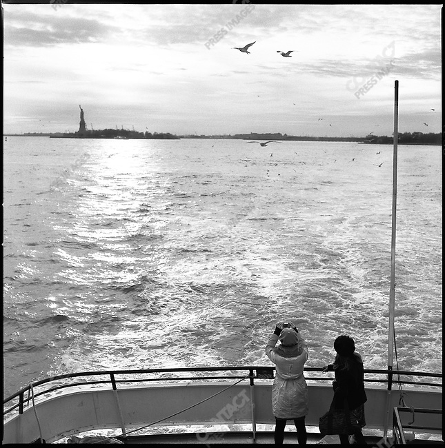 Passengers on a boat from Ellis Island to Manhattan looked back to Liberty Island and the Statue of Liberty. New York City, New York, November 12, 2008