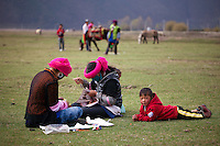 """May 1st, 2011_Shangri-La, Yunnan, China_ Ethnic Tibetans gather for a local festival, near the tiny village of Rime, near the town of Zhongdian (or Shangri-La) in northern Yunnan province, China.  Several of these families take advantage of """"Home Stays,"""" by opening their homes to visiting tourists.  Photographer: Daniel J. Groshong/The Hummingfish Foundation"""