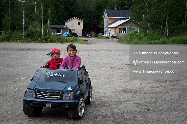 Two young aboriginals ride a toy car in the algonquin Anicinape community of Kitcisakik in Quebec, Canada, July 18, 2009. The aboriginals living in Kitcisakik, a small algonquin Anicinape community, don't have an official statue and are considered squatters by the crown. They don't have access to electricity and running water in their houses that are very modest.