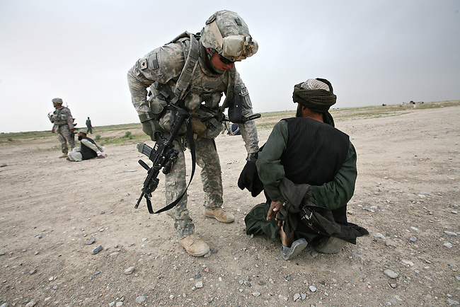 Spc. Robert Hausler, 24,  of Sarasota, Fla., a soldier with 2nd Battalion, 2nd Infantry Regiment, searches an Afghan man suspected of setting off a  roadside bomb in Maiwand district, Kandahar province, Afghanistan. March 28, 2009. DREW BROWN/STARS AND STRIPES