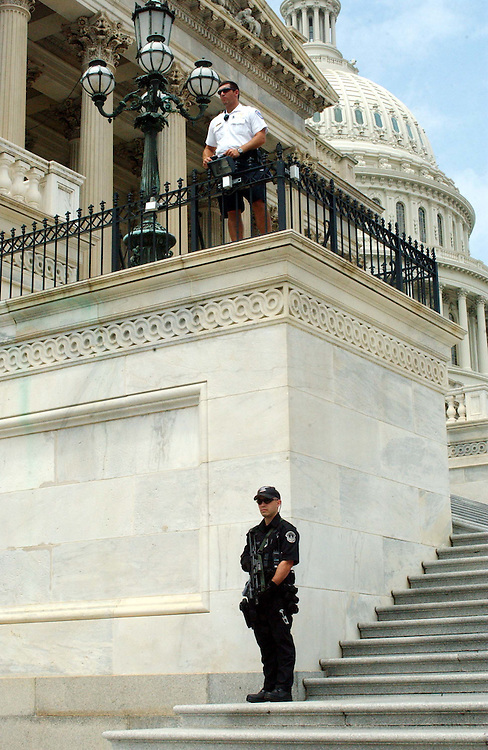 7/23/03.SECURITY--A U.S. Capitol Police, the one below carrying an automatic weapon, stand guard on the steps of the House side of the U.S. Capitol..CONGRESSIONAL QUARTERLY PHOTO BY SCOTT J. FERRELL