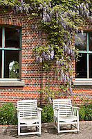 A pair of antique garden chairs in the cobbled courtyard