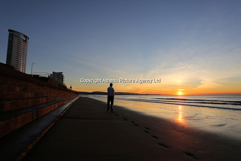 WEATHER PICTURE WALES<br /> Pictured: A young man takes a picture of the sun rises over Swansea Bay in Wales, UK. Wednesday 30 November 2016<br /> Re: Low temperatures with sunshine in most parts of the UK