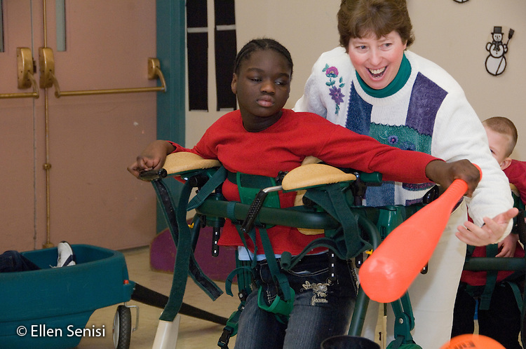 MR / Albany, NY.Langan School at Center for Disability Services .Ungraded private school which serves individuals with multiple disabilities.Physical Therapist assists child  in gait trainer during Adaptive Physical Education class (APE) game of T-ball. Girl: 10, African-American, cerebral palsy, expressive and receptive language delays.MR: Pie3; And6.© Ellen B. Senisi