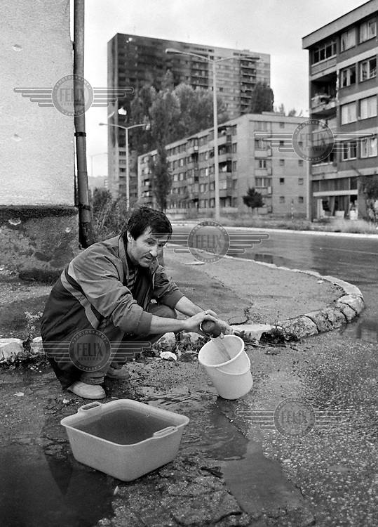 A man gathers rainwater from a puddle in the street in the besieged Bosnian capital Sarajevo on November 28 1993, while a block of flats burns from artillery shelling in the background. 350,000 Sarajevans have lived mostly without water, electricity and gas since April 1992.