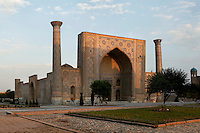 General view of Ulugh Beg Madradsah, 1417-20, Registan,  Samarkand, Uzbekistan, pictured on July 16, 2010, at dawn. The lancet arched portal of this Madradsah, commissioned by the scholarly Ulugh Beg, faces the square and high well-proportioned minarets flank the corners. Geometrically patterned mosaic surrounds the entrance arch. It was restored in the early twentieth century. Samarkand, a city on the Silk Road, founded as Afrosiab in the 7th century BC, is a meeting point for the world's cultures. Its most important development was in the Timurid period, 14th to 15th centuries. Picture by Manuel Cohen.