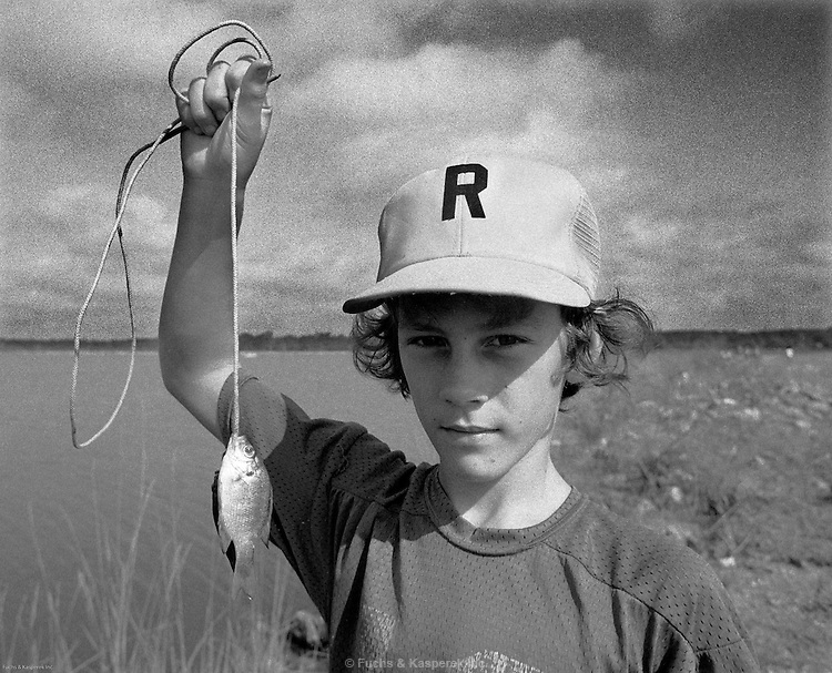 A boy poses with his catch during a fishing rodeo for kids at the Ross Barnett Reservoir near Jackson, Miss. 1979