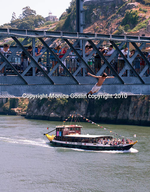 A boy jumps into the Douro River from the Don Luis iron bridge in Porto, Portugal.
