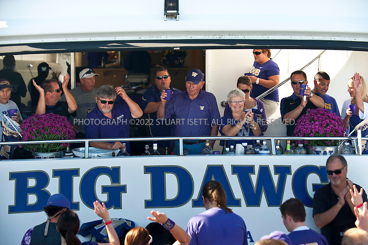 9/24/2011--Seattle, WA, USA...Frank Miles, 73, (center raising cup) listens as members of the UW marching band perform on Big Dawg, parked at docks next to Husky Stadium...The 'Big Dawg', owned by Lisa and Tim Kittilsby, is the biggest, most prominent boat that attends regular boat tailgate parties on docks near the UW (University of Washington) Husky Stadium. Up to 500 boats will tie up outside Husky Stadium on football game days, ranging from from small boats to huge yachts. The Big Dawg is a 92-foot, two-story yacht that dominates the tailgate parties...The tradition started when Lisa and Tim Kittilsby's parents, Frank and Jeanie Miles, took a 23-foot boat called The Mixer to a game over 40 years ago...©2011 Stuart Isett. All rights reserved.