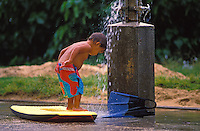 Child showering off after boogieboarding