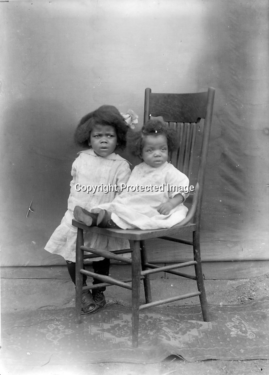 PAIRS OF SIBLINGS. It appears that John Johnson sometimes set up his open-air &quot;studio&quot; and families brought their children to him. It is difficult to be certain whether this image and image LB055 were taken the same day, but they were taken on the same rug and perhaps used the same chair. Baby boys and girls were often dressed similarly, but hair ribbons were huge and hugely popular for girls only.<br /> <br /> Photographs taken on black and white glass negatives by African American photographer(s) John Johnson and Earl McWilliams from 1910 to 1925 in Lincoln, Nebraska. Douglas Keister has 280 5x7 glass negatives taken by these photographers. Larger scans available on request.