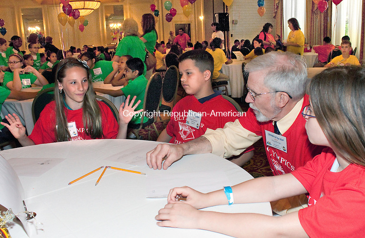 WATERBURY, CT.-30 JUNE 2013-060513DA01- Fifth grade students of Maloney Interdistrict Magnet School in Waterbury Olivia Pawlik, left, Dylan Senderoff, second from left, and Lillian DeGrosse, right, talk with the school's math resource teacher Paul Murray as they prepare for round 2 of the 10th Annual Olympics of the Mind held at the CoCo Key Resort Hotel &amp; Convention Center in Waterbury Wednesday. The competition was developed for third and fifth grade student in the Waterbury Public School District to provide a review of knowledge learned during the year and to prepare them for the Connecticut Mastery Test.<br /> Darlene Douty Republican-American