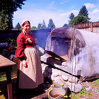 Fort Langley National Historic Site, BC, British Columbia, Canada - Re-enactment Woman Baker baking Bread in Historic Bake Oven.  Fort Langley was founded in 1827 as a Hudson's Bay Company Trading Post.