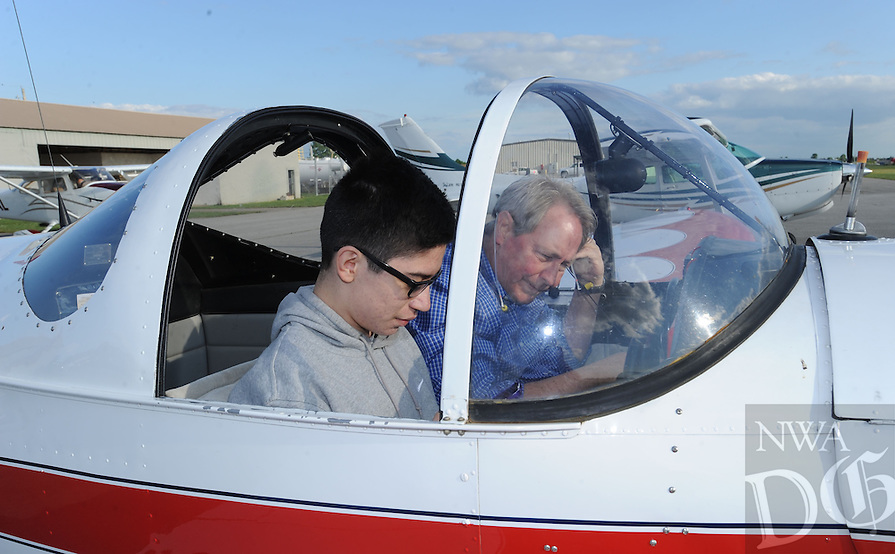NWA Democrat-Gazette/ANDY SHUPE<br /> Pilot Tim Keaten (right) helps student Fernando Lopez, 14, into an airplane before taking flight Wednesday, May 18, 2016, during the Wright Flight &quot;Fly Day&quot; at the Bentonville Municipal Airport. Pilots with The Tailwind Aviation Foundation flew with six students from Crossroads, Rogers&rsquo; alternative school. Each student earned the right to fly a plane when they fulfilled a written contract with the school to: accomplish an agreed upon goal; remain drug, alcohol and tobacco free; and complete a 9-hour aviation history course and pass an exam with an 85 percent or better grade.