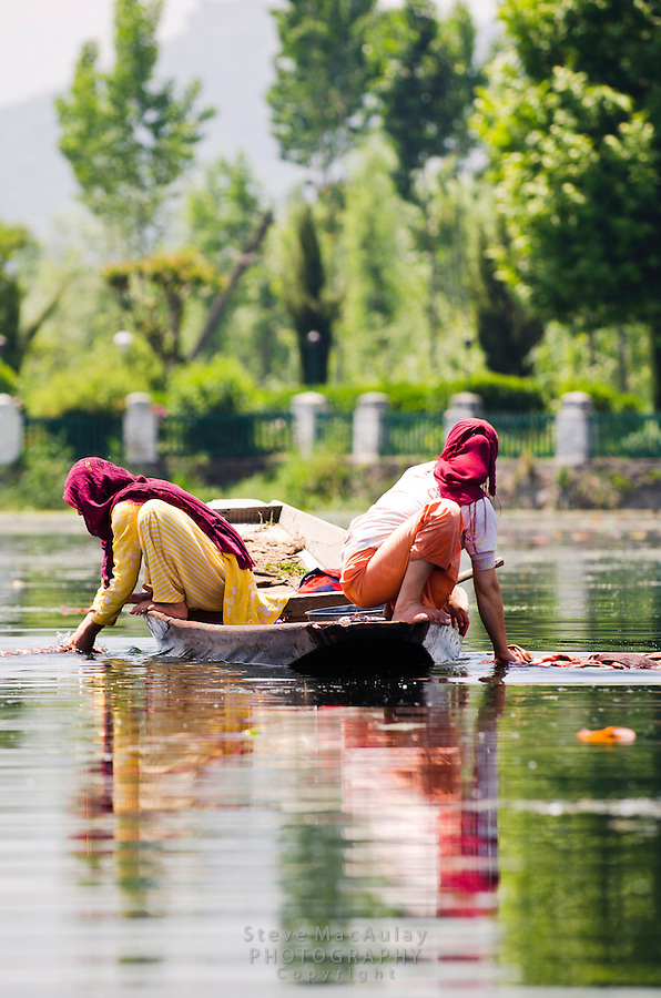 Kashmiri women in headscarves washing laundry from their traditional shikara, Dal Lake, Srinagar, Kashmir, India.