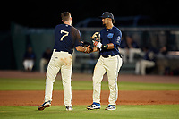 Mobile BayBears Roberto Baldoquin (27) hands Connor Justus (7) his glove and hat during a Southern League game against the Jacksonville Jumbo Shrimp on May 7, 2019 at Hank Aaron Stadium in Mobile, Alabama.  Mobile defeated Jacksonville 2-0.  (Mike Janes/Four Seam Images)