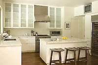 The large white kitchen has a marble work surface and central island that doubles as a breakfast bar