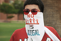 "Phoenix, Arizona (July 28, 2012) - About three hundred people marched to protest the second anniversary of the approval of some provisions of the SB 1070 immigration law. The march, called ""No Papers, No Fear"" was organized by immigrant rights groups who say the law discriminates people of brown skin. In this photograph, a young man who participated in the ""No Papers No Fear"" march wears a bandana to cover part of his face. The message printed in the bandana read: ""No Human Is Illegal"".  The march was held to oppose Arizona immigration law SB 1070 and racial profiling. Photo by Eduardo Barraza © 2012"