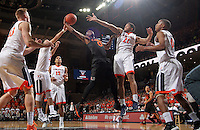 Miami guard Ja'Quan Newton (0) shoots between Virginia  defenders during the game Tuesday, Jan. 12, 2016 in Charlottesville, Va. Virginia defeated Miami 66-58. Photo/Andrew Shurtleff