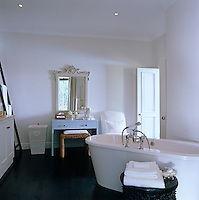 The bath is angled into the middle of the room in this contemporary white bathroom with a contrasting black wood floor