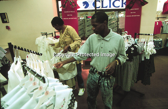 SBSHOPS31049 Shops. Black people looking at clothes in a clothing store. Clicks. Woolworths. 12/96.©Per-Anders Petterson/iAfrika Photos