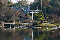 The exterior of the Shinto shrine seen from across the lake at the Suizen-ji garden, Kumamoto, Japan