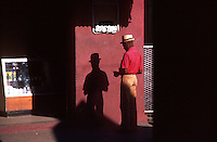 Shadow of man with pork pie hat checking his wallet, Bridge town Barbados, Caribbean,