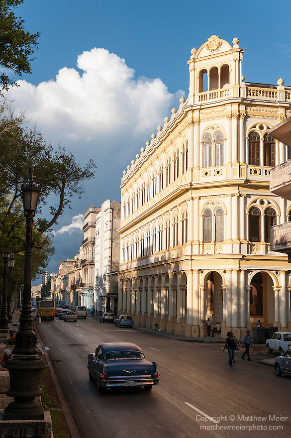 Havana, Cuba; a 1957 Cadillac drives down the Paseo del Prado past colonial building facades in late afternoon sunlight