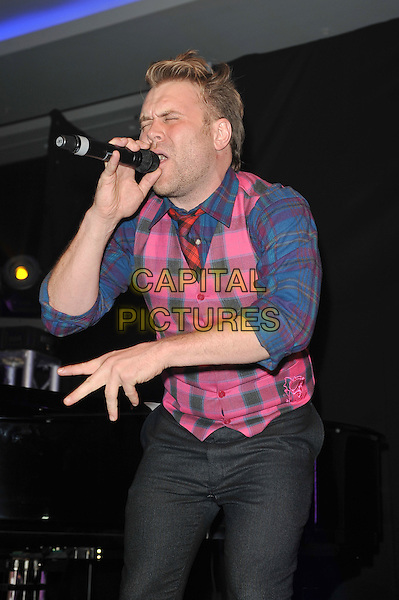 Daniel Bedingfield.'Global Angels Awards', The Park Plaza Hotel, Westminster, London, England. 2nd December 2011..music on stage live concert gig performing half length pink blue tartan plaid shirt waistcoat red tie  grey gray trousers hand microphone singing eyes shut  funny .CAP/MAR.© Martin Harris/Capital Pictures.
