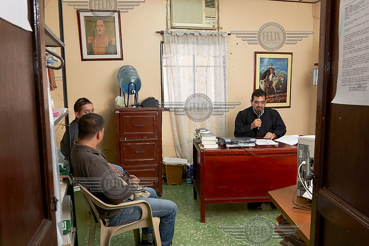 The judge of the Juzgado 1ero Promiscuo del Circuito in the municipality of Turbaco reads out a verdict in public, as required by Colombian law. The audience consists of two policemen. After this reading, they will go out to arrest the four men now being sentenced to 54 months each for aggravated robbery.