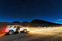 Photographer Ethan Tweedie stands near his car under the stars at the summit of Mauna Kea on the Big Island.