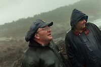 December 13, 2011 - Laxe (La Coruña). Julio and Feuto - a retired percebeiro - inspect the condition of the sea. It's the second day of harvesting, but not even the gale force eight and heavy rains can stop them, Christmas' time is too important. © Thomas Cristofoletti 2011