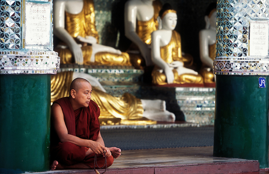 A monk sits at the Shwedigon Pagoda, one of the holiest sites for Buddhists, Yangon, Burma, 2006.
