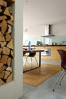 "In the kitchen a chestnut wood ""carpet"" has been inset into the concrete floor and the table and kitchen cupboards are made of the same wood"