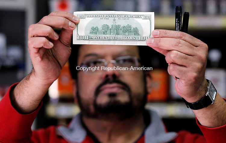 Waterbury, CT- 02, March 2011-030211CM08 Yogesh Bhagat, owner of Sullivan's Discount Liquors in Waterbury looks at a hundred dollar bill at his store.  Bhagat said he checks security measures within the bills to validate their authenticity.   Christopher Massa Republican-American