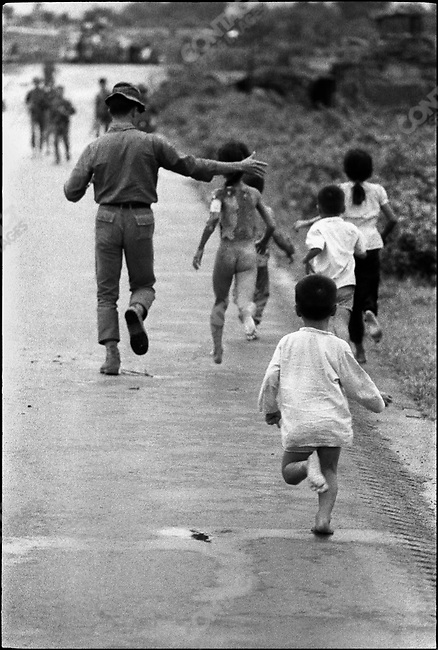 Phan Thi Kim Phuc, her body seared by napalm. The iconic image by Associated Press photographer Nick Ut was taken moments before. David Burnett who was standing next to him had exposed his film. He quickly reloaded his camera and took this picture as the nine-year-old girl (naked, from the back) ran for shelter with her brothers and sister. Trang Bang, South Vietnam, June 8, 1972