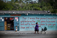 Street scene. Nauruans are fervent Christian believer. Nauru, officially the Republic of Nauru is an island nation in Micronesia in the South Pacific.  Nauru was declared independent in 1968 and it is the world's smallest independent republic, covering just 21 square kilometers..Nauru is a phosphate rock island and its economy depends almost entirely on the phosphate deposits that originate from the droppings of sea birds. Following its exploitation it briefly boasted the highest per-capita income enjoyed by any sovereign state in the world during the late 1960s and early 1970s..In the 1990s, when the phosphate reserves were partly exhausted the government resorted to unusual measures. Nauru briefly became a tax haven and illegal money laundering centre. From 2001 to 2008, it accepted aid from the Australian government in exchange for housing a Nauru detention centre, with refugees from various countries including Afghanistan and Iraq..Most necessities are imported on the island..Nauru has parliamentary system of government. It had 17 changes of administration between 1989 and 2003. In December 2007, former weight lifting medallist Marcus Stephen became the President.