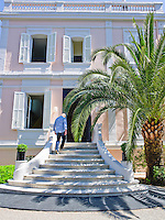 Designer Jason Maclean ascends the curved steps leading up to his pink and white villa in Cannes