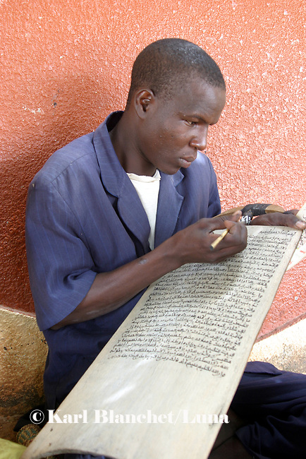 Talibe writing coranic versets on wooden boards, Niger. In Niger, coranic schools still exist and are very traditional. Talibe, pupils, even go and beg for money and food in the afternoon in order to pay the marabout.