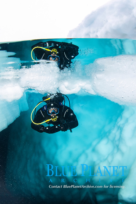 Spit image of a scuba diver diving close to an iceberg, only in springtime, when the hard winter slowly subsides, are the ice-cold waters suitable for divers who can dive around a iceberg that floats in crystal-clear water, Tasiilaq, Greenland, North Atlantic Ocean