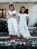"April 15th 2004-Ermera, Timor-Leste-Two young girls dressed in their ""Sunday finest,"" wait outside the church in the town of Ermera for services to begin.  Ermera Town, in Ermera District is famous for it's many coffee plantations. Photograph by Daniel J. Groshong/Tayo Photo Group"